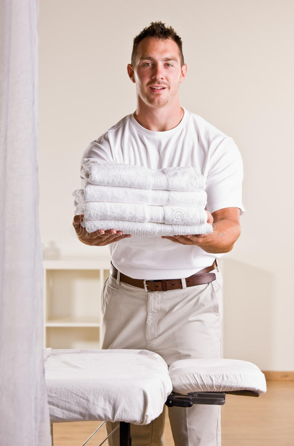 Massage therapist holding stack of towels. Massage therapist holding out a stack of towels stock photography