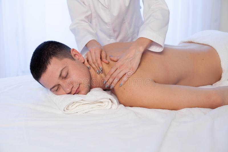 A massage therapist makes therapeutic massage of hands and neck in Spa. Medicine stock photography