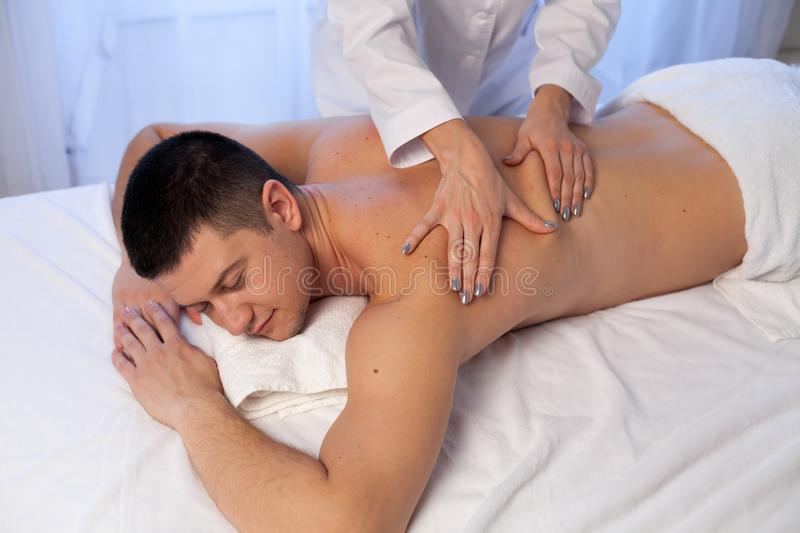 A massage therapist makes therapeutic massage of hands and neck in Spa. Medicine royalty free stock photography