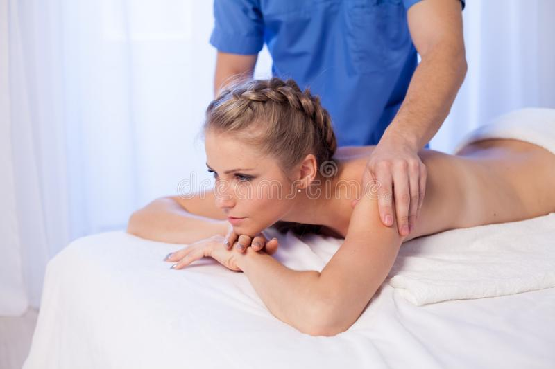 A massage therapist makes therapeutic massage of hands and neck in Spa medicine. A massage therapist makes therapeutic massage neck in Spa medicine stock image