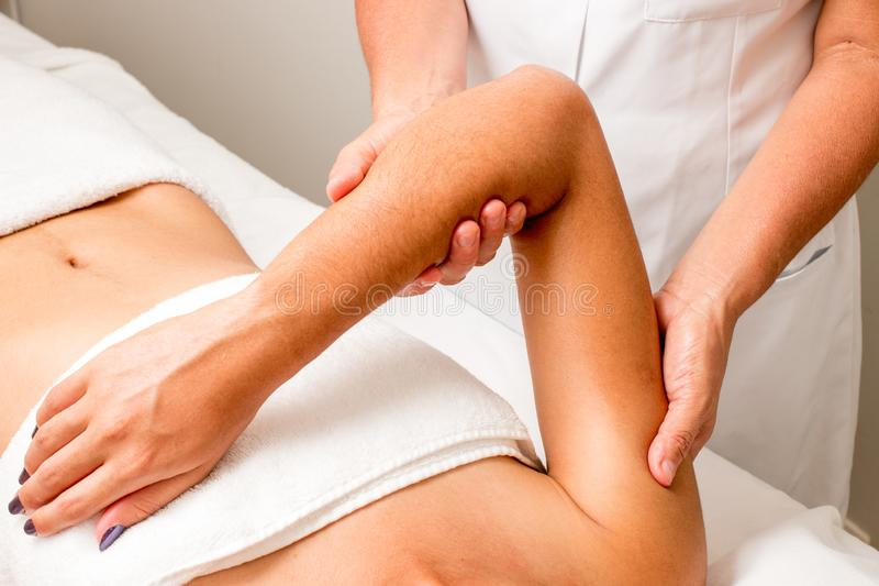 Massage Therapist Massaging a Woman`s Arms stock photography
