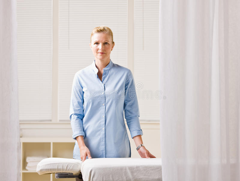 Massage therapist next to massage table stock photography