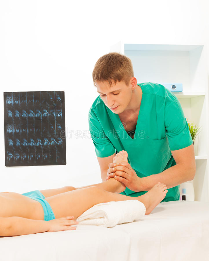 Massage therapist performing therapy. The recreation therapist acupressure little boy's feet at light massage room royalty free stock photo