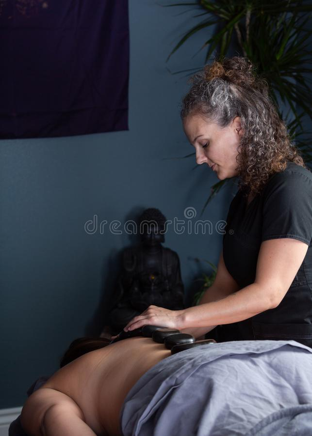 Massage therapist standing to right of client royalty free stock photo