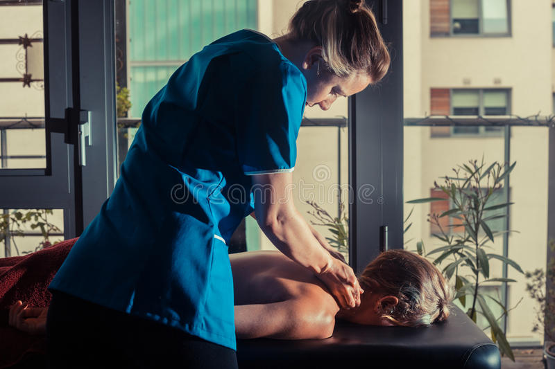 Massage therapist treating a client royalty free stock photography