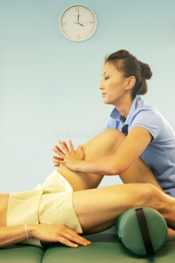 Massage therapy - leg massage stock images