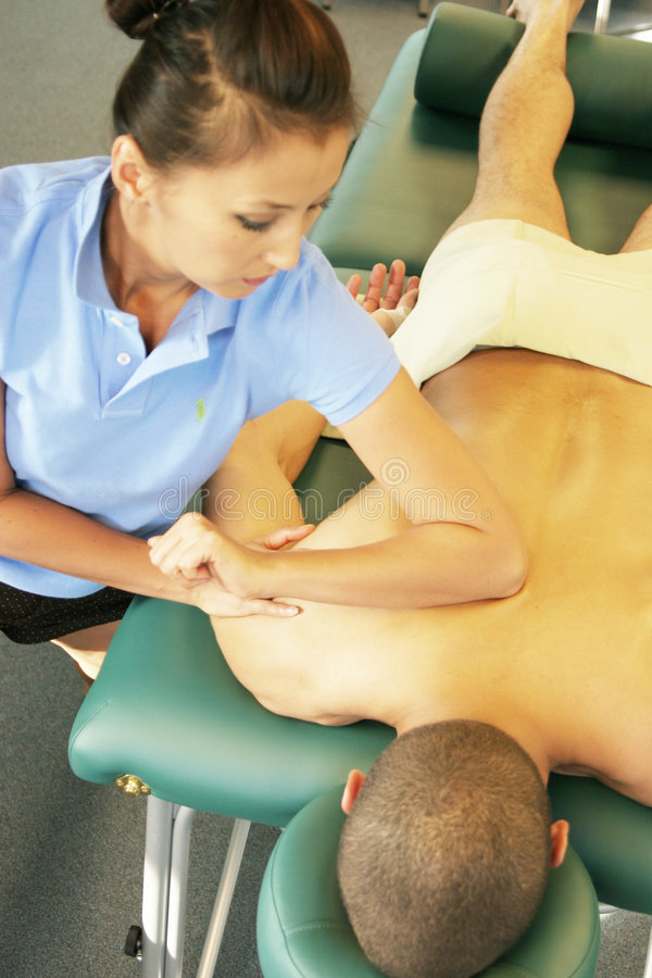 Massage therapy - therapist giving deep tissue massage royalty free stock image