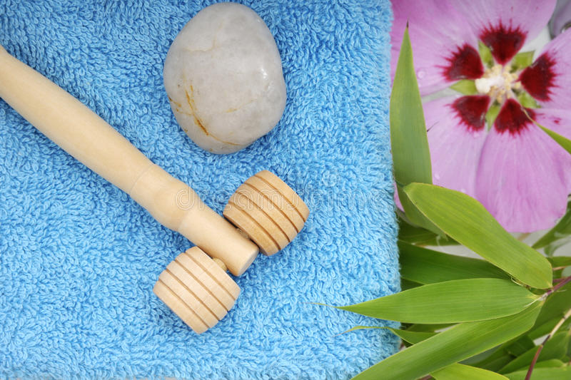 Massage therapy tools. On a blue spa towel with hibiscus flower and bamboo leaves stock photo