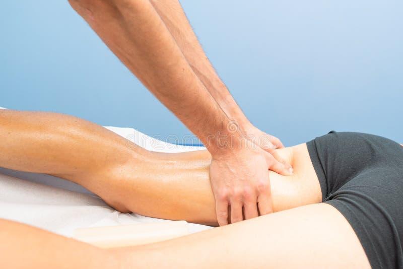 Massage till låret av en fysioterapeut till en idrottsman nen royaltyfri bild
