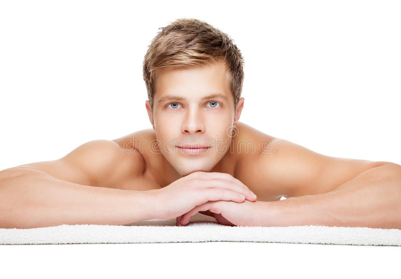 Massage treatment. Handsome man ready for massage treatment isolated on white stock photo