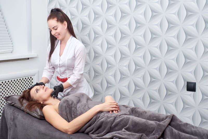Massage und Gesichtsbehandlung zieht am Salon unter Verwendung der Kosmetik ab stockfoto
