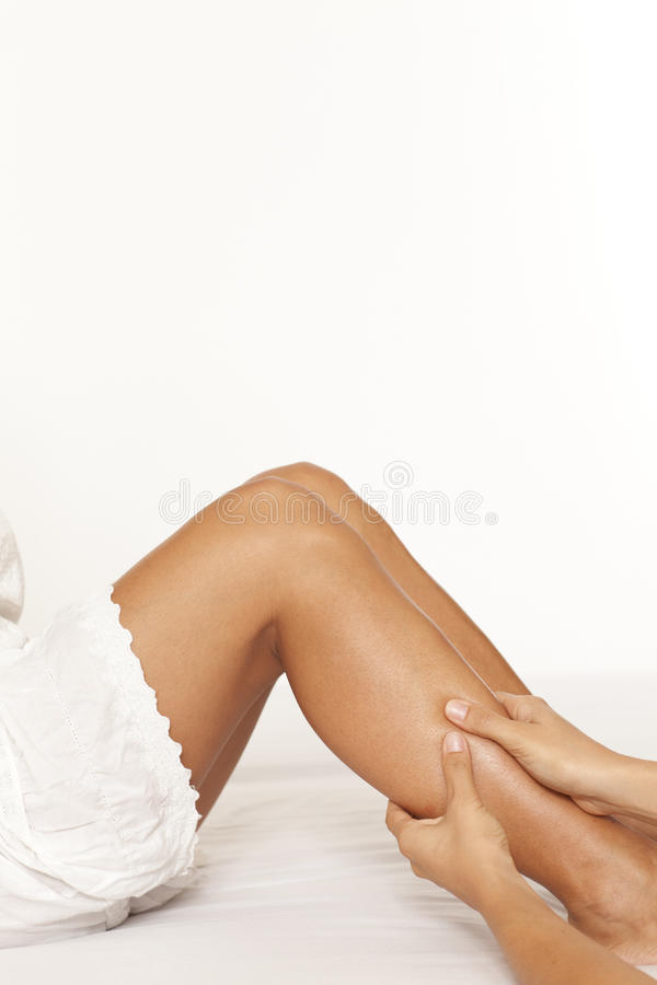 Massage of a woman calf muscle. On white background royalty free stock photos