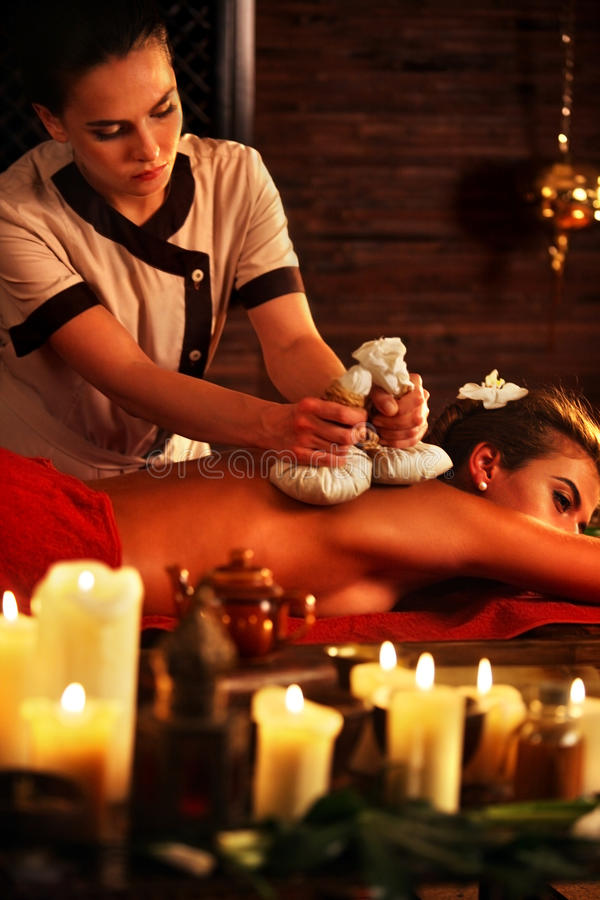 Massage woman spa salon. Female have herbs hot ball therapy. Aromatherapy massage of women in spa salon. Girl ayurvedic herbs massaging spa salon. Luxary royalty free stock image