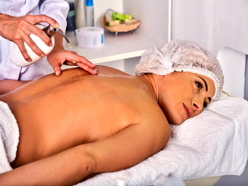 Massage woman therapist making manual therapy back. Hands of masseuse close up. Treatment of spinal injuries 40 old client in spa salon. Beautician uses stock photography