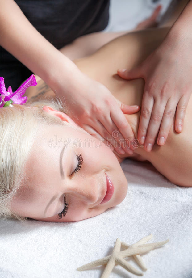 Massage for young beautiful woman in the spa salon royalty free stock photography