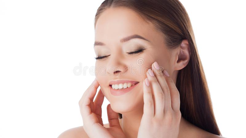 Massage your face. Use face cream and serum. Portrait of young beautiful woman isolated on white. stock image