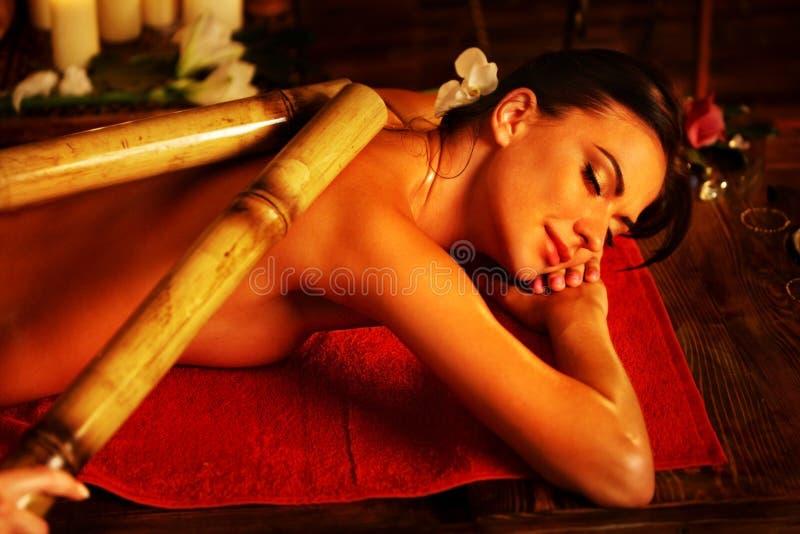 Massagem de bambu da mulher no salão de beleza dos termas Terapia oriental interior fotos de stock royalty free