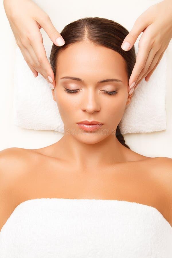Massagem de cara. Close-up de uma jovem mulher que obtém o tratamento dos termas. fotos de stock