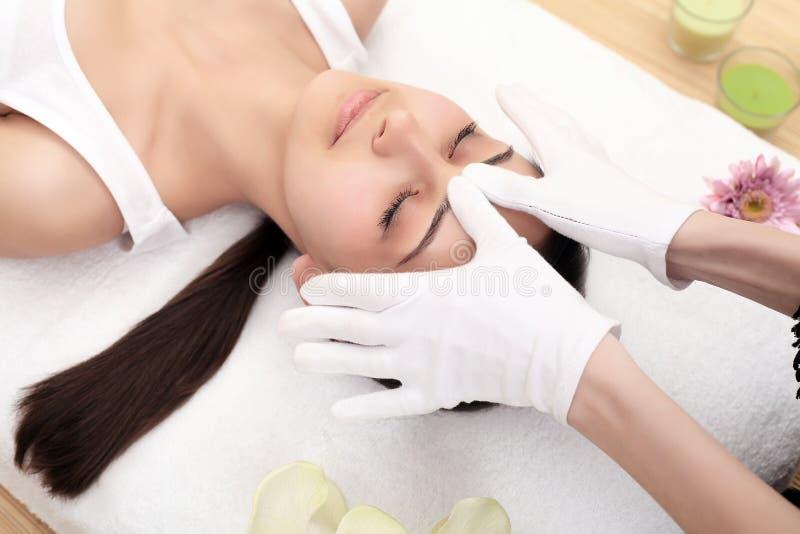 Massagem de cara Close-up de uma jovem mulher que obtém o tratamento dos termas fotografia de stock
