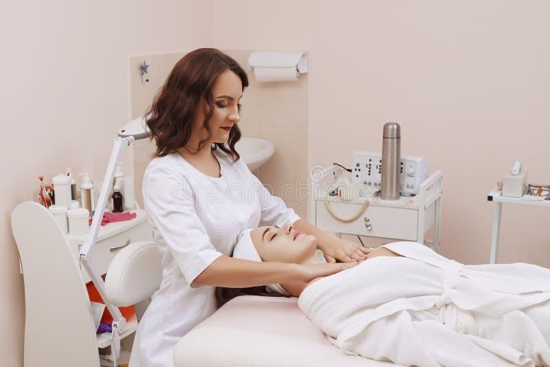Massagem de cara de uma jovem mulher que obtém o tratamento dos termas fotos de stock