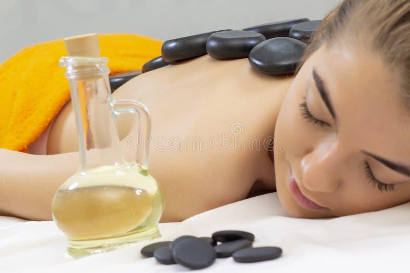 Massagem de pedra quente dos termas Menina bonita atrativa que encontra-se na cama da massagem na terapia do aroma dos termas do  fotografia de stock royalty free