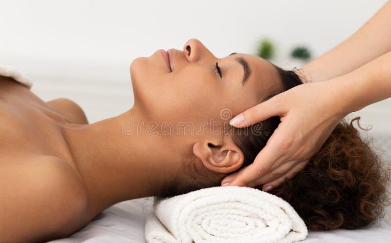 Massagem de relaxamento Mulher do Afro que recebe a massagem principal foto de stock royalty free