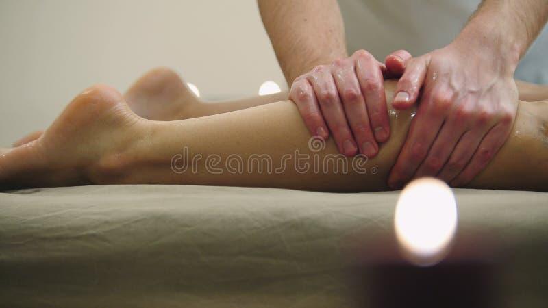 Massagem do óleo de sésamo para o músculo da vitela Tratamento para a fêmea nova, fim do abrandamento acima foto de stock royalty free