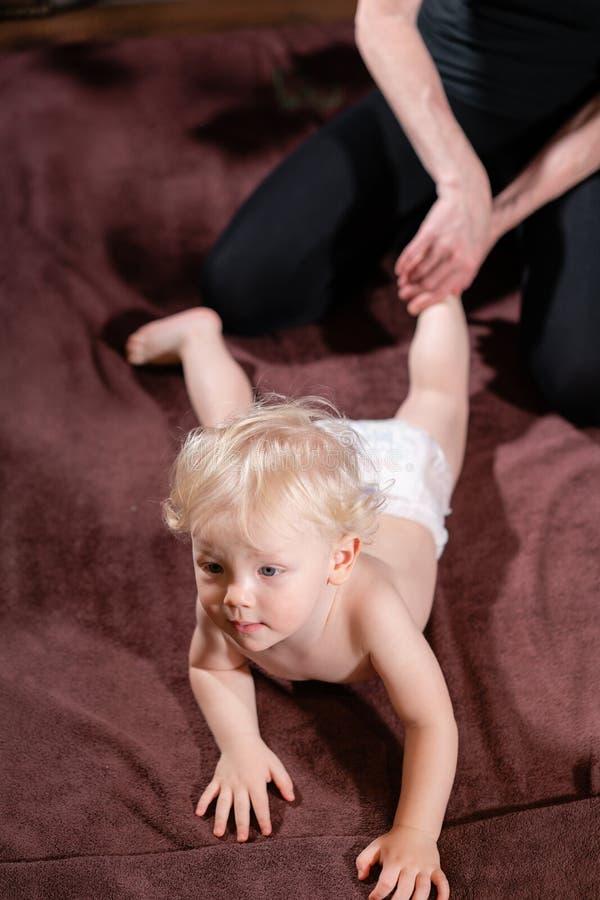 Massagem do bebê A mãe ou o terapeuta fazem a massagem do pé a seu bebê em casa Conceito dos cuidados médicos e da medicina Menin imagem de stock