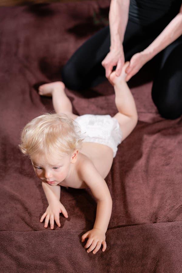 Massagem do bebê A mãe ou o terapeuta fazem a massagem do pé a seu bebê em casa Conceito dos cuidados médicos e da medicina Menin fotografia de stock