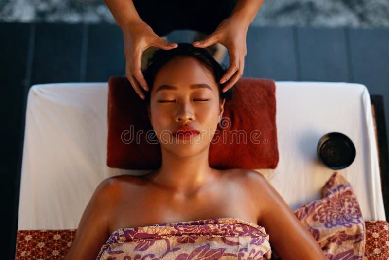 Massagem dos termas Mãos que fazem massagens a cabeça da mulher no salão de beleza tailandês imagens de stock