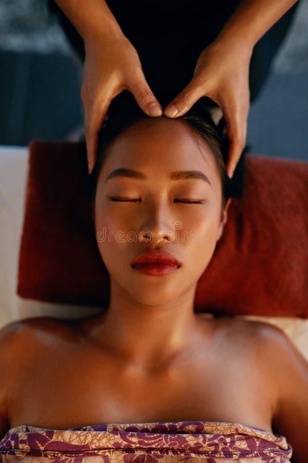Massagem dos termas Mãos que fazem massagens a cabeça da mulher no salão de beleza tailandês foto de stock royalty free