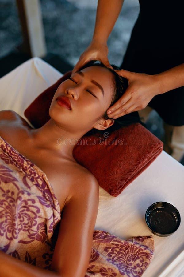 Massagem dos termas Mãos que fazem massagens a cabeça da mulher no salão de beleza tailandês imagem de stock royalty free