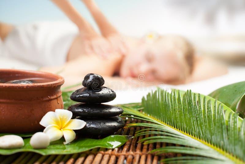 Massagem dos termas sob a palma tropical Jovem mulher bonita que obt?m a massagem dos termas imagens de stock royalty free