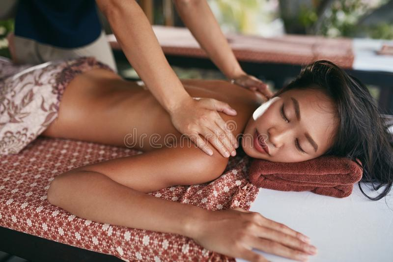 Massagem traseira em termas tailandeses Mulher que tem a massagem do corpo no salão de beleza fotografia de stock