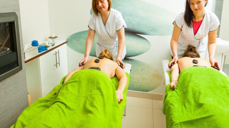 Massagen med varmt vaggar stenar i kosmetolog royaltyfria bilder