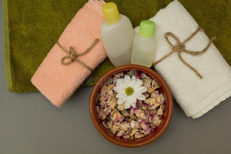 Massageolja på kulöra handdukar, blomma arkivbild