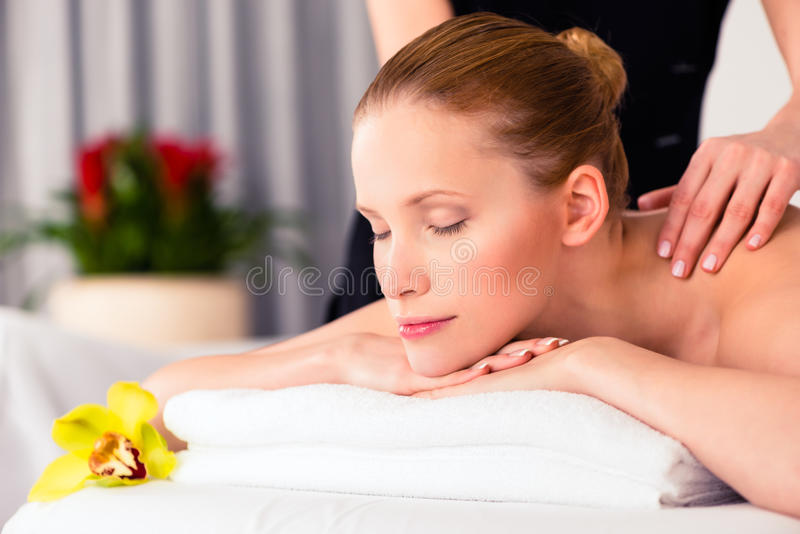 Massager giving woman wellness spa massage. Massager giving women in wellness beauty spa back massage with essential oil stock photo