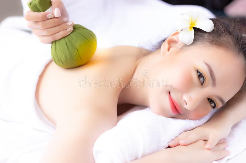 Massager rejuvenate and massage charming beautiful woman's back by using herbal ball. Attractive girl feels relaxed and happy. Beautiful lady gets satisfied royalty free stock photos