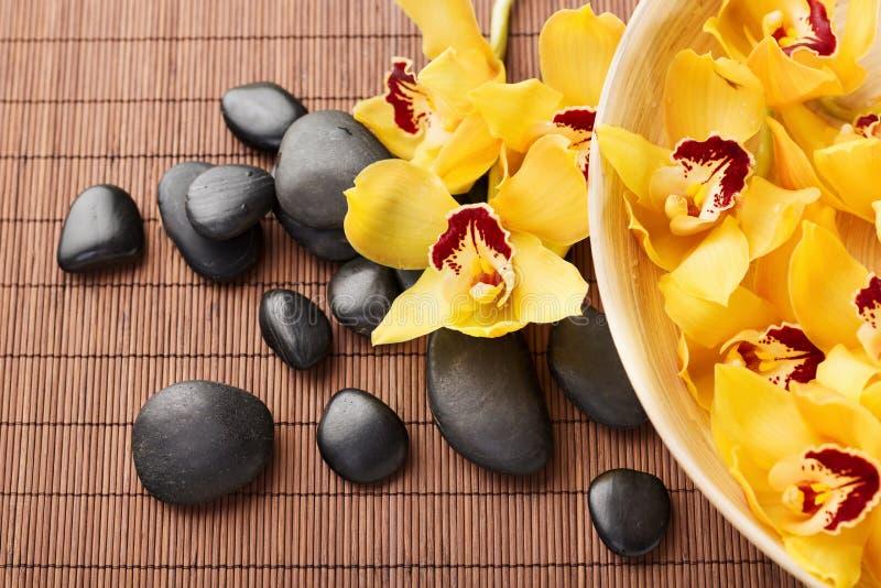 Massagesteine mit Blumen auf Matte stockbilder