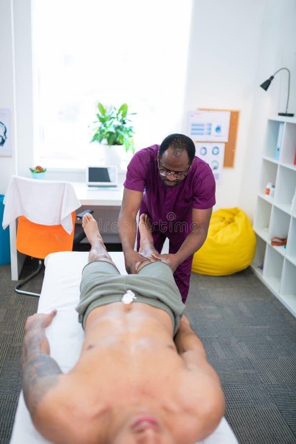 Massageterapeut i enhetliga massera ben för idrottsman royaltyfri fotografi