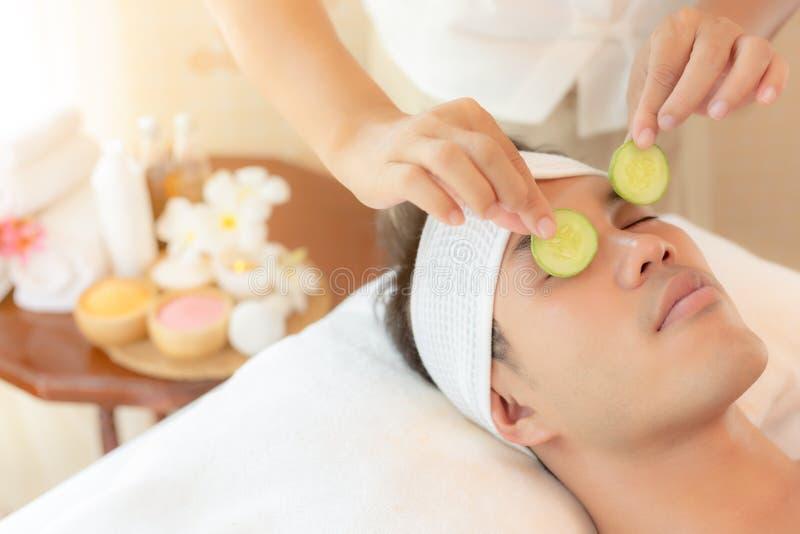 Massageterapeut som använder gurkaskivor som sätts till stiliga unga asiatiska manögon för återställandefuktighet av ögonhud och  royaltyfri bild