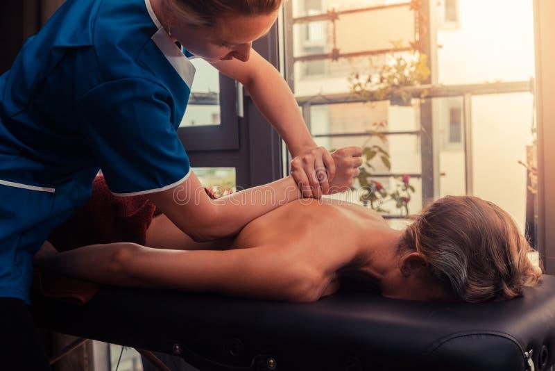 Massageterapeut som behandlar en klient arkivbild