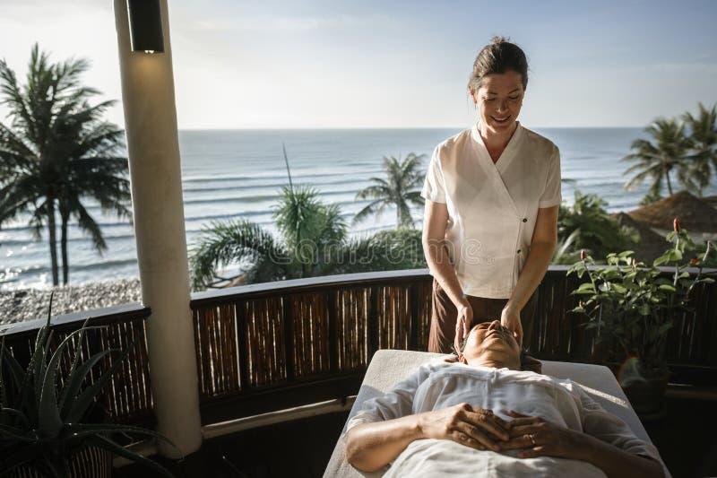 Massageterapeut som masserar på en brunnsort arkivfoto
