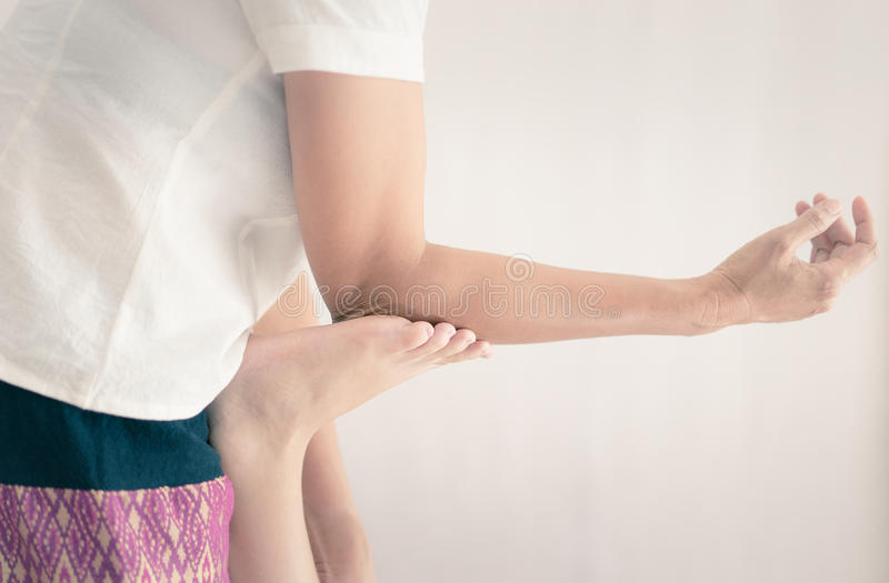 Massageterapeuten använder armbågen för att skjuta på fot royaltyfri foto