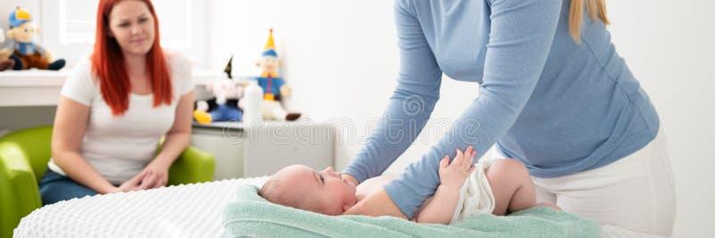 Massagetherapeut bei Frauen oder Arzt, der einen Neugeborenen untersucht und dabei die Mutter im Hintergrund beobachtet Babymassa stockbild