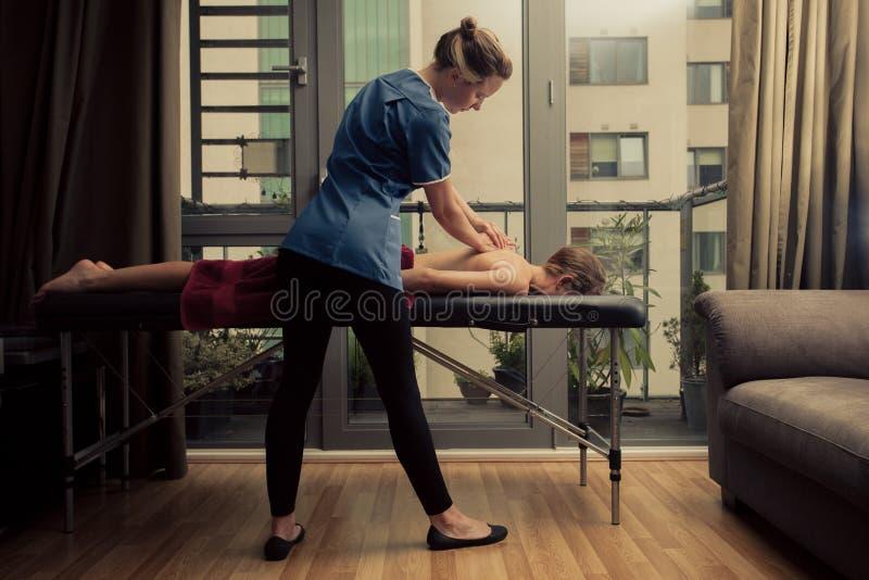 Massagetherapeut, der zu Hause Patienten behandelt stockfotos