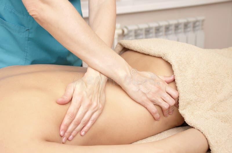 Massagetherapeut die een therapeutische achtermassage voor een vrouw doen stock foto's