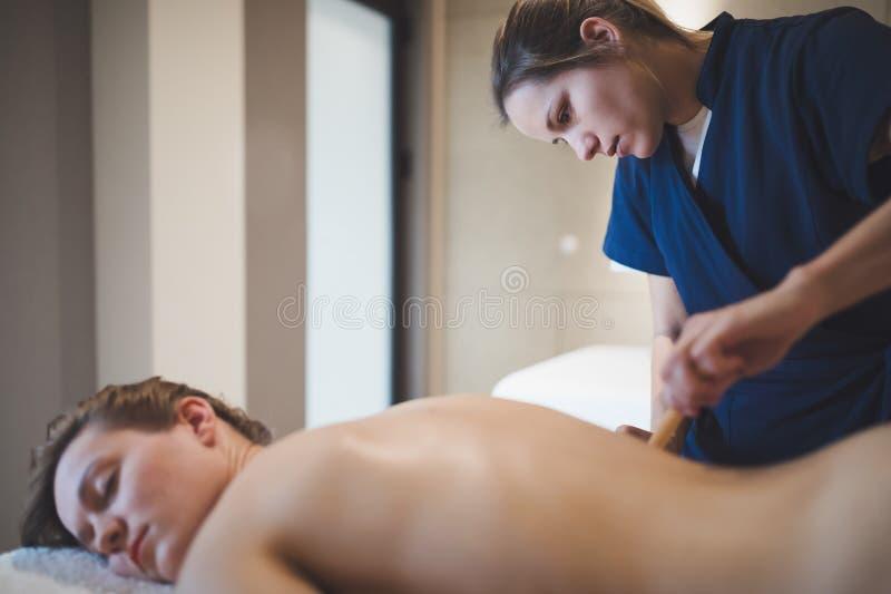 Massagetherapeut die houten hulpmiddel met behulp van om patiënt te masseren stock afbeelding