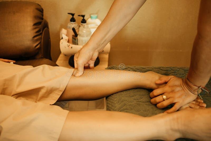 Massaggi il massaggio del corpo del fondo nella giovane donna del salone della stazione termale precisa immagine stock