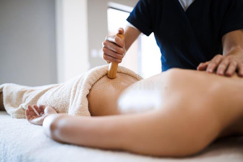 Massaggiatore che cura massaggiatrice al salone di benessere fotografie stock libere da diritti